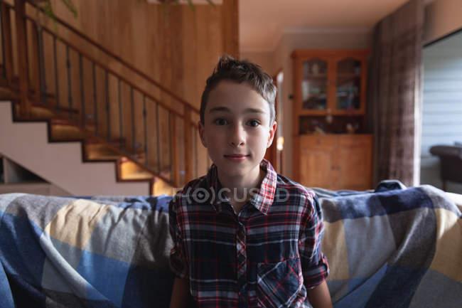 Porträt eines vorpubertären kaukasischen Jungen, der auf einer Couch in einem Wohnzimmer zu Hause sitzt und in die Kamera blickt — Stockfoto