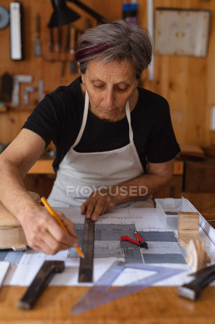 Front view close up of a senior Caucasian female luthier measuring on a workbench in her workshop, with tools hanging up on the wall in the background — Stock Photo