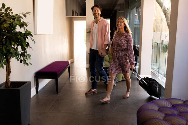 Vista dianteira de um par caucasiano novo feliz que relaxa no feriado que chega com as malas de viagem a um hotel, prendendo as mãos — Fotografia de Stock