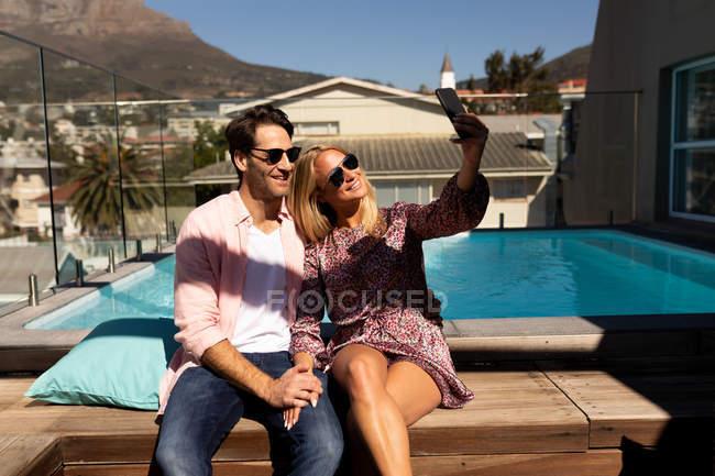 Vista frontal de um jovem casal caucasiano feliz relaxando de férias sentado à beira de uma piscina, tirando uma selfie — Fotografia de Stock