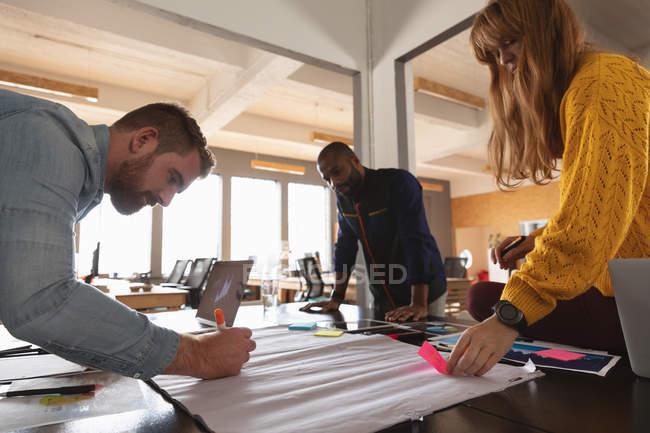 Vista laterale da vicino di un giovane uomo afroamericano e di un giovane uomo e donna caucasici in piedi e appoggiati a una scrivania che lavorano insieme a un progetto in un ufficio creativo — Foto stock