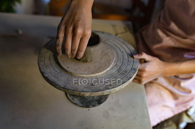 Elevated close up of the hands of female potter shaping clay into a pot on a banding wheel in a pottery studio — Stock Photo
