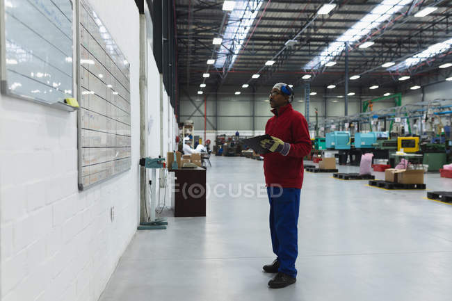 Side view of a middle aged African American male factory worker holding a clipboard checking information on a whiteboard in a warehouse at a processing plant — Stock Photo
