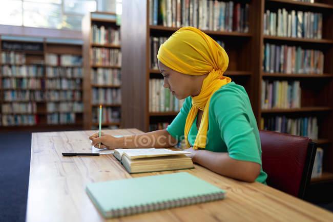 Vue de côté gros plan d'une jeune étudiante asiatique portant un hijab prenant des notes et étudiant dans une bibliothèque — Photo de stock