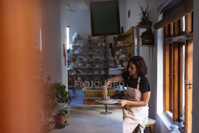 Side view of a young Caucasian female potter sitting at a work table in front of a window, working with clay on a banding wheel in a pottery studio — Stock Photo