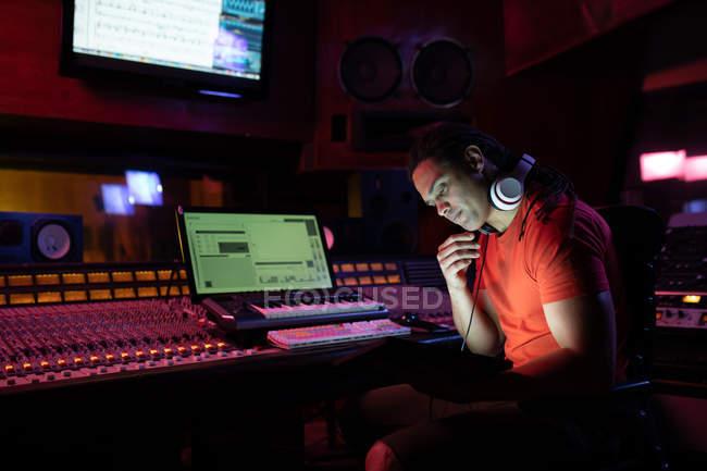 Vista lateral de perto de um jovem engenheiro de som misto sentado e trabalhando em uma mesa de mistura usando um computador portátil em um estúdio de gravação — Fotografia de Stock