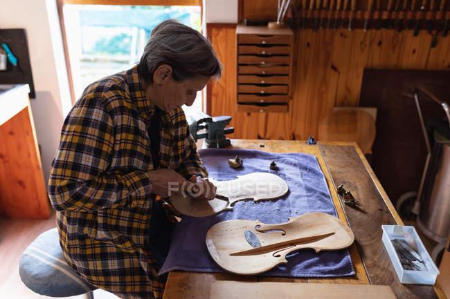 Vista lateral de um luthier feminino caucasiano sênior trabalhando no corpo de um violino com ferramentas penduradas na parede no fundo — Fotografia de Stock