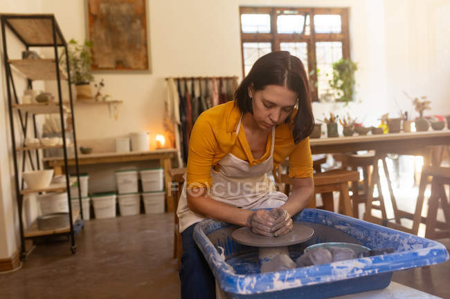 Front view of a young Caucasian female potter sitting and working with clay on a potters wheel in a pottery studio — Stock Photo