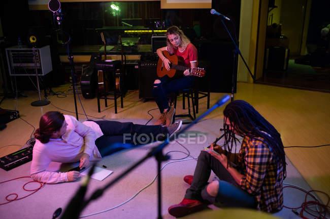 Vista frontal de uma jovem caucasiana sentada em um banquinho tocando uma guitarra acústica, enquanto um jovem caucasiano se deita no chão ouvindo ela e um jovem mestiço se senta no chão escrevendo — Fotografia de Stock