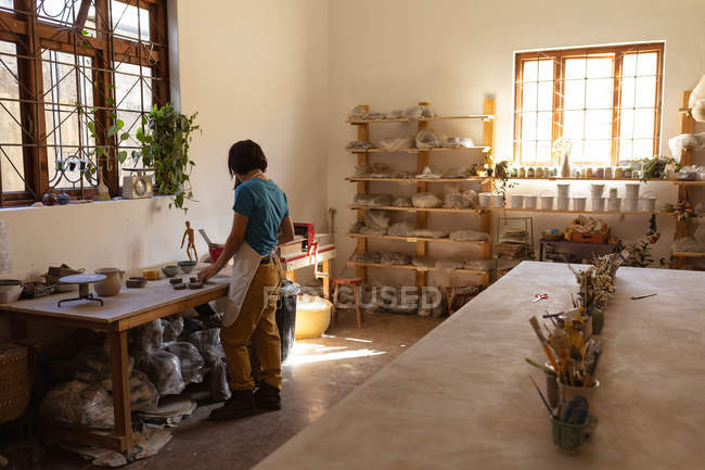 Rear view of a young Caucasian female potter working with pieces of clay standing at a work table in front of a window in a pottery studio — Stock Photo