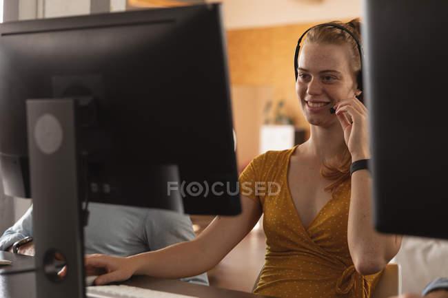 Вид спереди на улыбающуюся молодую кавказскую женщину, сидящую за столом за компьютером и разговаривающую на телефонной гарнитуре в креативном кабинете, замеченном между экранами компьютеров — стоковое фото