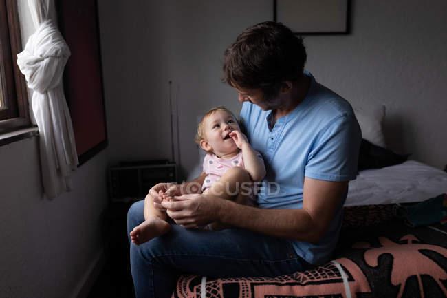 Передній вигляд молодого кавказького батька, який тримає своє немовля, сидячи на ліжку і дивлячись один на одного. — стокове фото