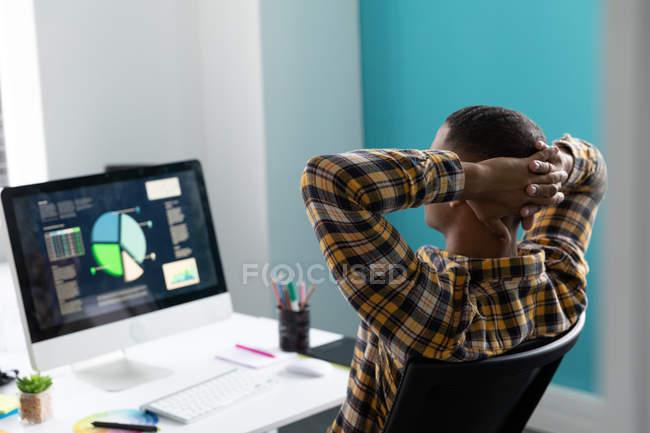 Vue arrière gros plan d'un jeune Afro-Américain assis à un bureau les mains derrière la tête, regardant un moniteur d'ordinateur dans le bureau moderne d'une entreprise créative — Photo de stock