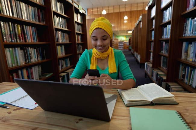 Вид спереди на молодую азиатскую студентку в хиджабе, держащую смартфон с помощью ноутбука и занимающуюся в библиотеке — стоковое фото