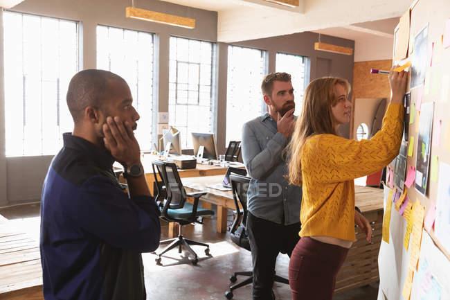 Сторона зору закривається між молодим афроамериканцем і молодим кавказьким чоловіком, який стоїть і дивиться, як їхні молоді кавказькі колеги пишуть на дошці ідей під час командного мозкового засідання в творчому кабінеті. — стокове фото