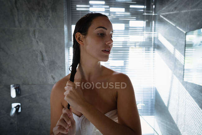 Front view close up of a young Caucasian brunette woman conditioning her hair and turning her head away from camera, standing in a modern bathroom with light streaming in through a window blind behind her — Stock Photo