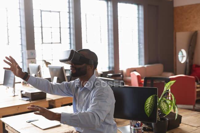 Вид сбоку на молодого афроамериканца, сидящего на столе в наушниках с вытянутыми руками и протянутыми руками в креативном офисе — стоковое фото