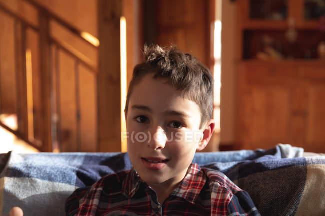 Портрет крупным планом молодого белого мальчика, сидящего на диване в гостиной дома, смотрящего в камеру — стоковое фото