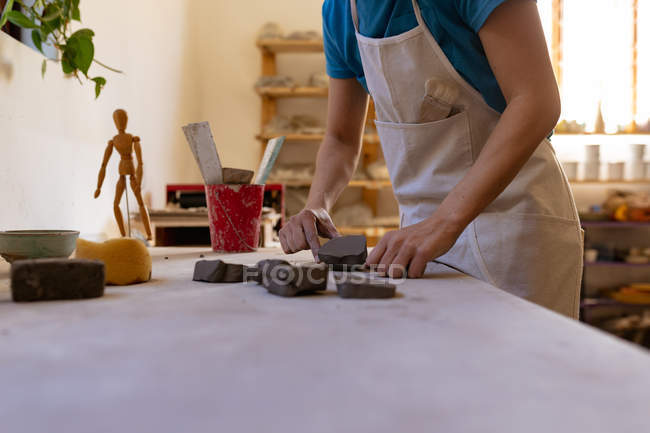Side view mid section of female potter wearing an apron working with pieces of clay at a work table in a pottery studio — Stock Photo