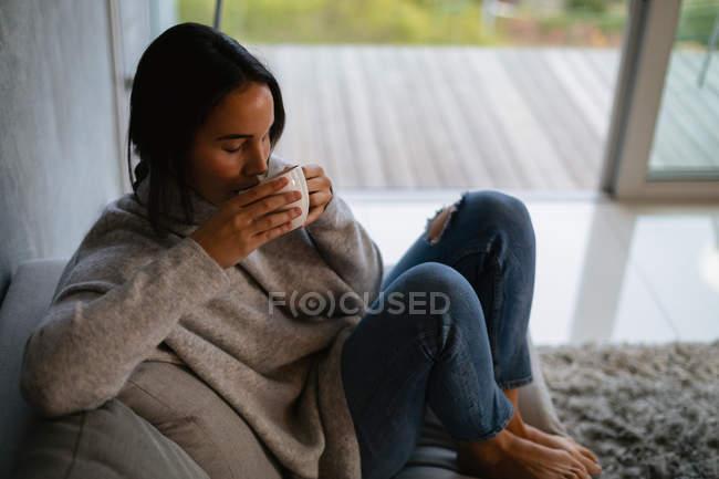 Vista elevata di una giovane donna bruna caucasica seduta su un divano con le gambe disegnate godendo di una tazza di caffè — Foto stock