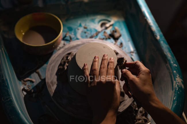 Elevated close up of the hands of female potter using a tool to shape the base of a bowl on a potters wheel in a pottery studio — Stock Photo