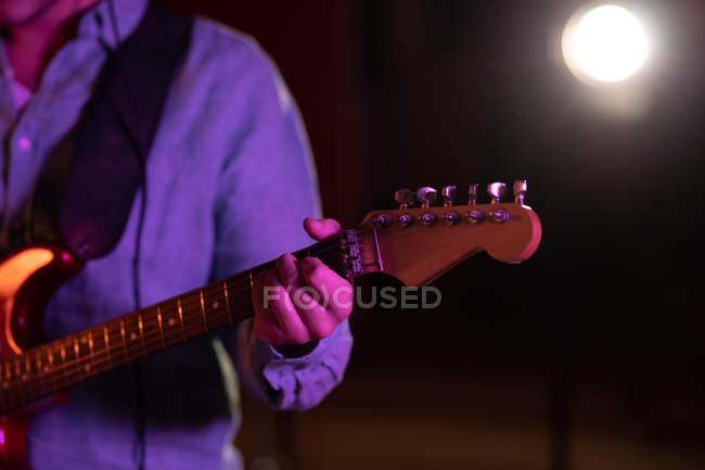 Frontansicht mittlere Sektion eines Mannes, der während einer Session in einem Tonstudio eine E-Gitarre spielt — Stockfoto