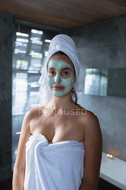 Портрет молодой белой женщины, одетой в банное полотенце и пакет для лица с завернутыми в полотенце волосами, смотрящей в камеру улыбающейся — стоковое фото