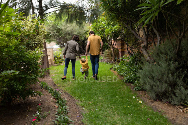 Rear view of a young Caucasian father and mother holding hands with their baby and walking in a garden — Stock Photo