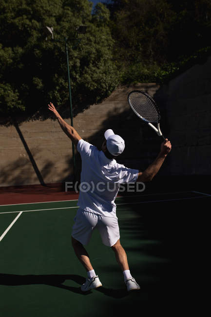 Rear view of a young Caucasian man playing tennis on a sunny day, serving with a wall behind him — Stock Photo