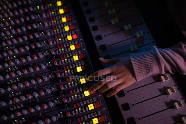 Overhead view of the hand of female sound engineer operating a mixing desk in a recording studio — Stock Photo