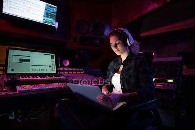 Front view of a young Caucasian female sound engineer sitting and working at a mixing desk in a recording studio using a laptop computer and wearing headphones — Stock Photo