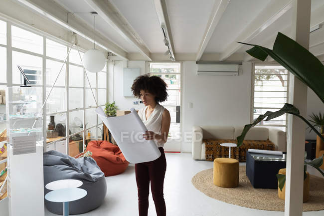 Front view of a young mixed race woman standing and checking an architectural drawing at a creative office — стокове фото