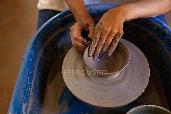 Elevated close up of the hands of female potter shaping wet clay into a bowl shape on a potters wheel in a pottery studio — Stock Photo