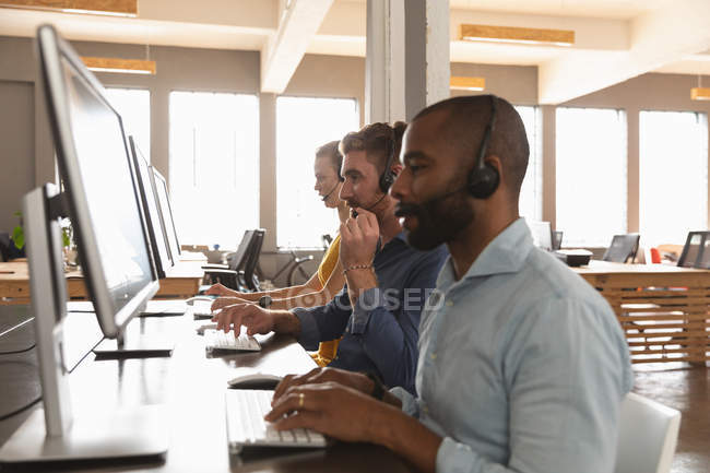 Side view close up of a young African American man and a young Caucasian woman and man sitting at desks using computers and talking on phone headsets in a creative office — Stock Photo