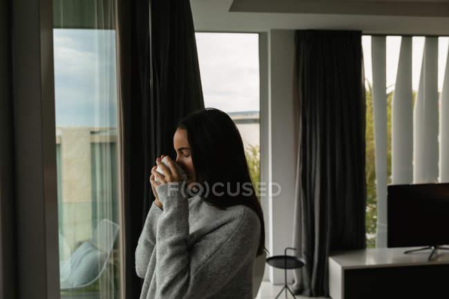 Vue latérale d'une jeune femme brune caucasienne portant un pull gris, debout près d'une fenêtre buvant une tasse de café les yeux fermés — Photo de stock