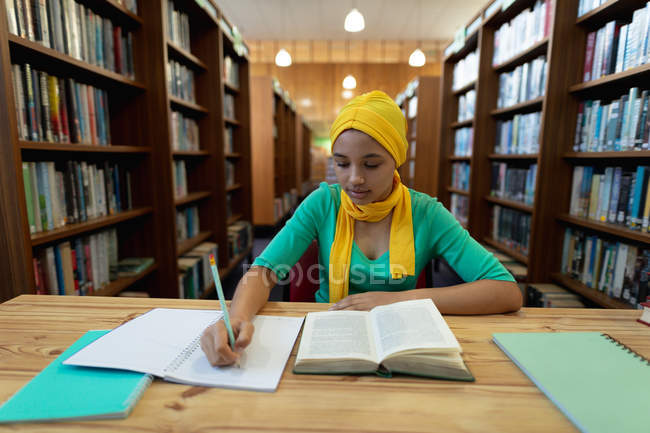 Nahaufnahme einer jungen asiatischen Studentin, die einen Hijab trägt, Notizen macht und in einer Bibliothek studiert — Stockfoto
