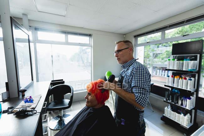 Vue latérale d'un coiffeur masculin caucasien d'âge moyen et d'une jeune femme caucasienne ayant ses cheveux colorés de rouge vif et séchés dans un salon de coiffure — Photo de stock