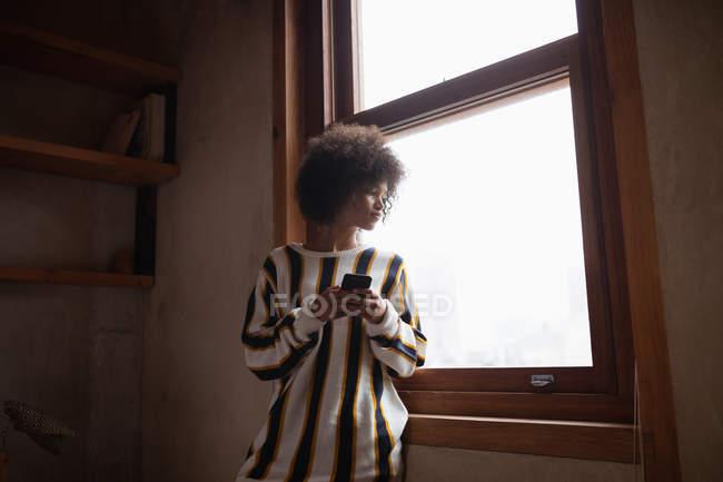 Вид спереди на молодую женщину смешанной расы, стоящую и смотрящую в окно дома, используя смартфон — стоковое фото