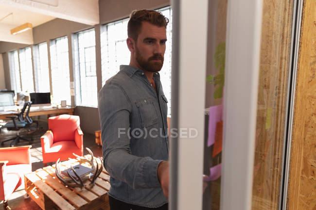 Vista frontal close-up de um jovem caucasiano lendo notas em uma parede e pensando durante uma sessão de brainstorm em equipe em um escritório criativo — Fotografia de Stock