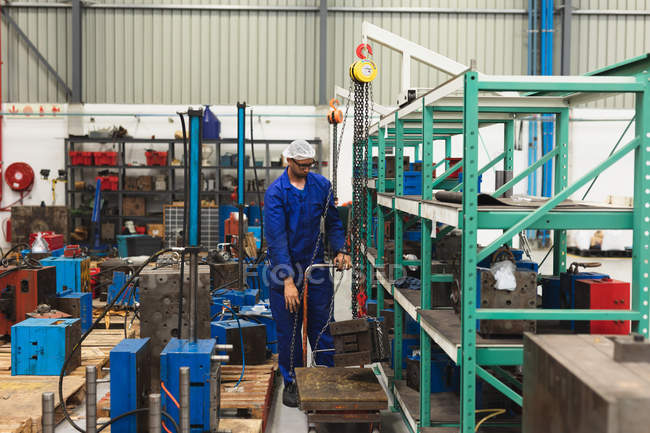 Front view of a middle aged mixed race male factory worker wearing glasses and workwear moving machine parts on a trolley in a storage area in a warehouse at a processing plant, with shelves of parts and equipment in the background — Stock Photo
