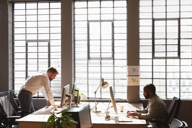 Vista laterale di un giovane afroamericano seduto a una scrivania che lavora al computer e di un giovane caucasico alla scrivania di fronte che usa un computer vicino alla finestra in un ufficio creativo — Foto stock