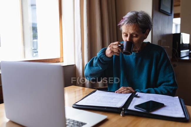 Вид спереди пожилой белой женщины, сидящей за столом дома и пьющей кофе со смартфоном и ноутбуком перед ней — стоковое фото