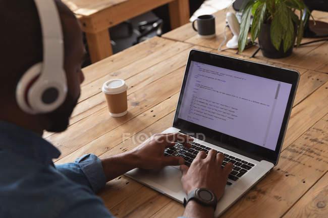 Par-dessus l'épaule d'un jeune Afro-Américain assis à un bureau portant un casque et travaillant sur un ordinateur portable dans un bureau créatif — Photo de stock