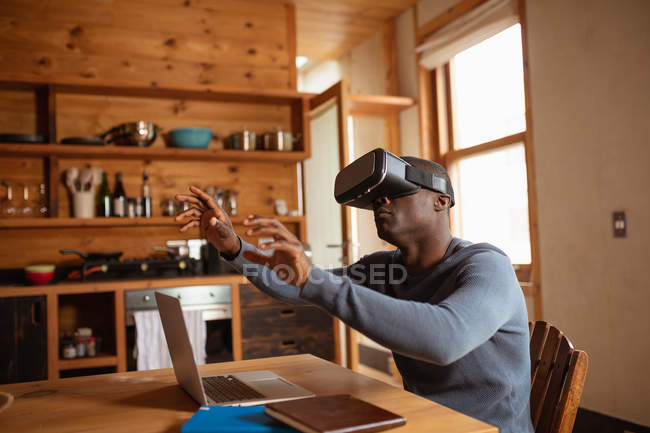 Side view close up of a young African American man wearing a VR headset sitting at the kitchen table at home with a laptop, with his arms raised and hands outstretched — Stock Photo