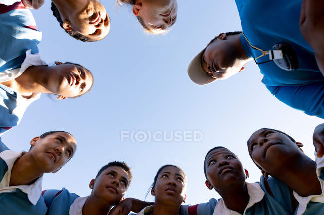 Low angle view looking up at a team of young adult multi-ethnic female rugby players and their middle aged mixed race female coach standing in a huddle on a rugby field with arms linked preparing for a rugby match — Stock Photo