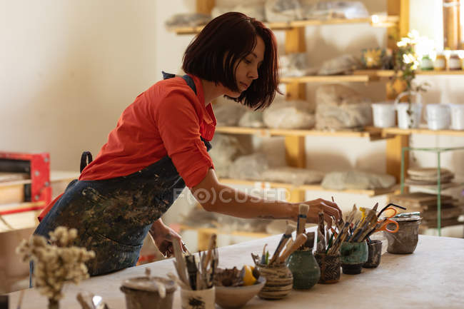 Side view of a young Caucasian female potter standing and selecting a tool from pots of tools on a work table in a pottery studio — Stock Photo