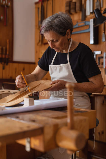 Side view close up of a senior Caucasian female luthier working on the body of a violin on a workbench in her workshop, with tools hanging up on the wall in the background — Stock Photo