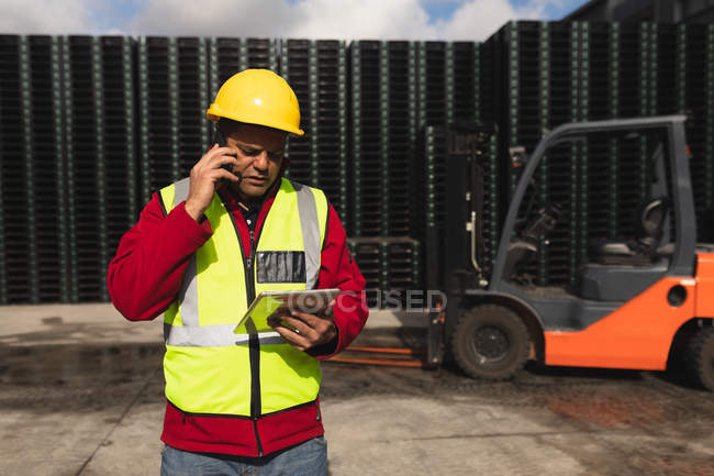Front view close up of a middle aged Caucasian male factory worker on the phone using a tablet computer beside a forklift truck and stacks of pallets outside a warehouse at a factory — Stock Photo