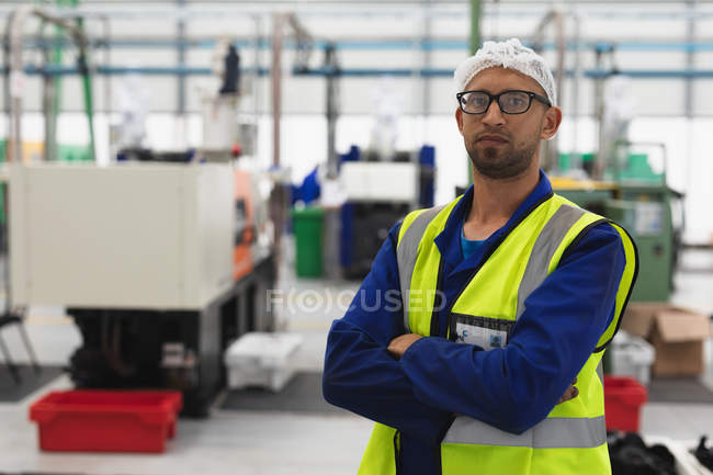Portrait close up of a middle aged mixed race male factory worker wearing glasses and workwear looking to camera with arms crossed in a warehouse at a processing plant — Stock Photo