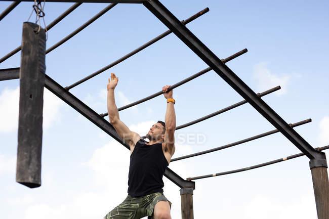 Vue de face d'un jeune homme caucasien grimpant aux barres de singe dans une salle de gym extérieure lors d'une séance d'entraînement de bootcamp — Photo de stock